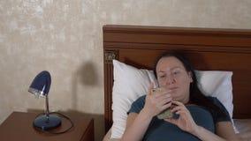 Donna turbata che esamina smartphone e che si trova a letto video d archivio