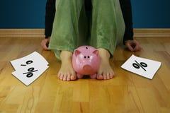 Donna turbata che si siede su un pavimento vuoto che tiene un porcellino salvadanaio e Fotografia Stock