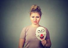 Donna turbata con la maschera triste del pagliaccio della tenuta di espressione che esprime felicità fotografie stock
