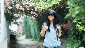 Donna turistica abbastanza giovane felice in cappello che cammina giù la via di vecchia città archivi video