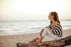 Donna turistica che esamina la distanza mentre sedendosi su un woode fotografie stock libere da diritti