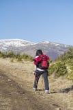 Donna turistica che fa un'escursione in un'alta montagna di inverno Fotografie Stock