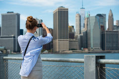 Donna turistica che prende l'immagine di viaggio con la macchina fotografica dell'orizzonte dell'orizzonte e di New York di Manha Fotografia Stock Libera da Diritti