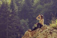 Donna turistica che riposa sulla roccia Fotografia Stock