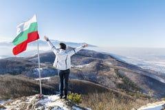 Donna turistica con a braccia aperte in un'alta montagna vicino alla bandiera bulgara Immagini Stock Libere da Diritti