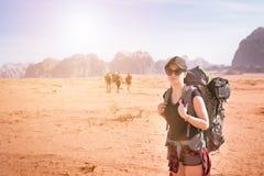 Donna turistica con gli amici in un deserto Parco naturale Wadi Rum della Giordania Viaggiatore con zaino e sacco a pelo sulla st Fotografia Stock