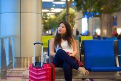 Donna turistica coreana felice ed abbastanza asiatica che si siede al portone di imbarco di partenza dell'aeroporto con il flig a immagine stock
