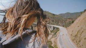 Donna turistica di vista posteriore del primo piano giovane con capelli che volano nella vista stupefacente di sorveglianza del f video d archivio