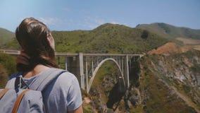 Donna turistica emozionante dei giovani posteriori di vista con lo zaino che guarda paesaggio epico al ponte iconico del canyon d stock footage