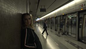 Donna turistica sul sottopassaggio nel sottosuolo che guarda alla macchina fotografica Giovane donna del ritratto sul treno in at video d archivio