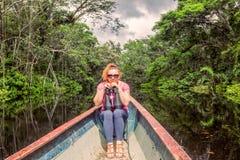 Donna turistica in una canoa con alto potere binoculare immagini stock