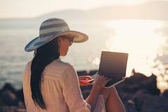 Donna turistica in vacanza che gode online con un computer portatile dal mare Fotografia Stock Libera da Diritti