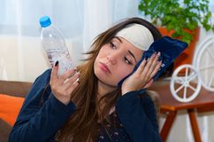Donna ubriaca con una maschera di occhio di sonno in sua testa e aplying una borsa di ghiaccio in sua testa facendo uso della sua fotografia stock