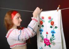 Donna ucraina che appende l'asciugamano ricamato Fotografie Stock Libere da Diritti