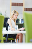 Donna in ufficio che esamina smartphone Immagine Stock