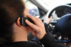 Donna in un'automobile che comunica su un telefono Fotografia Stock Libera da Diritti