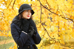 Donna in un black hat su fondo dell'albero di autunno Fotografie Stock
