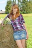 Donna in un campo con le balle di fieno Fotografie Stock Libere da Diritti