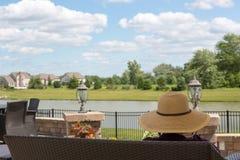 Donna in un cappellino da sole che si siede su un banco del patio Fotografie Stock Libere da Diritti