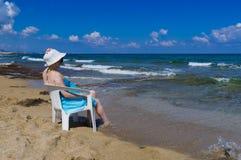 donna in un cappello che si siede sulla spiaggia Immagini Stock