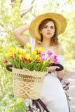 Donna in un cappello su una bicicletta fotografia stock