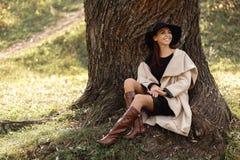 Donna in un cappotto beige e seduta black hat sotto l'albero immagini stock