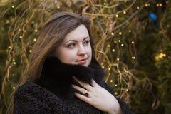 Donna in un cappotto caldo sui precedenti delle luci Fotografia Stock Libera da Diritti