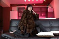 Donna in un cappotto di pelliccia sul sofà Fotografia Stock