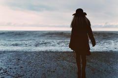 Donna in un cappotto nero sulla spiaggia Fotografia Stock