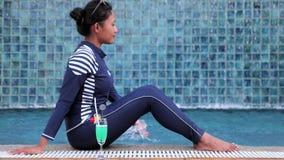 donna in un costume da bagno del interamente corpo allo stagno blu video d archivio