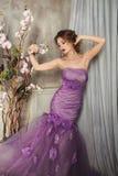 Donna in un fiore lilla dell'orchidea della tenuta del vestito Immagini Stock Libere da Diritti