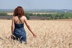 Donna in un giacimento di grano un giorno di estate fotografie stock