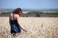 Donna in un giacimento di grano un giorno di estate fotografia stock
