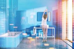 Donna in un interno blu del bagno tonificato Immagine Stock