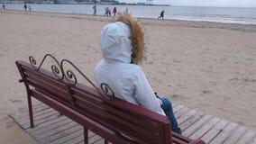Donna in un piumino bianco che si siede su un banco sulla spiaggia e esaminare la distanza Inverno del mare, vista posteriore archivi video