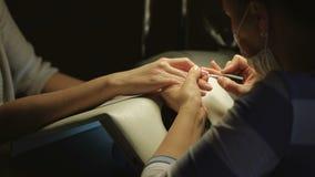 Donna in un salone dell'unghia che riceve manicure da un estetista Concetto di trattamento di bellezza stock footage