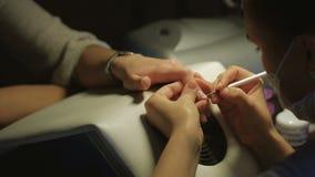 Donna in un salone dell'unghia che riceve manicure da un estetista Concetto di trattamento di bellezza archivi video