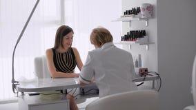 Donna in un salone dell'unghia che riceve un manicure da un estetista Donna che ottiene il manicure dell'unghia video d archivio