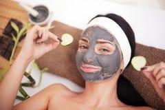 Donna in un salone di bellezza, benessere Fronte cosmetico del ` s della donna di procedura attenuarsi della maschera e nelle fet Fotografie Stock