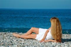 Donna in un tovagliolo su una spiaggia fotografia stock libera da diritti