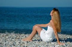 Donna in un tovagliolo sulla spiaggia immagine stock libera da diritti