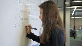 Donna in un ufficio sulla lavagna dal testo di scrittura dell'indicatore in inglese stock footage