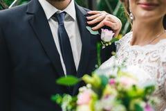 Donna in un vestito bianco lungo con un mazzo di nozze con uno sposo barbuto fotografia stock libera da diritti
