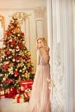 Donna in un vestito color crema lungo, stando vicino all'albero di Natale ed alla porta La bionda lussuosa in vestito da sera cel fotografia stock libera da diritti