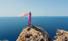 Donna in un vestito lungo che sta su un mare della roccia Fotografia Stock