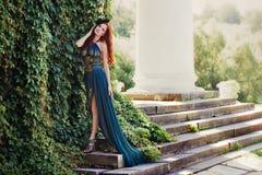 Donna in un vestito lungo che sta sui punti della proprietà terriera Fotografie Stock Libere da Diritti