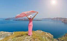 Donna in un vestito lungo che sta in un campo delle margherite Immagini Stock