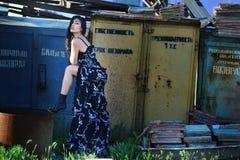 Donna in un vestito lungo con capelli marroni lungamente scorrenti e la gamba piegata contro il contesto dei magazzini abbandonat Immagine Stock