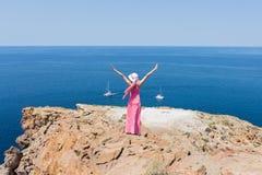 Donna in un vestito lungo da estate che sta su una scogliera Immagine Stock Libera da Diritti