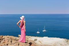 Donna in un vestito lungo da estate che sta su una scogliera La Grecia, Santo Immagine Stock Libera da Diritti